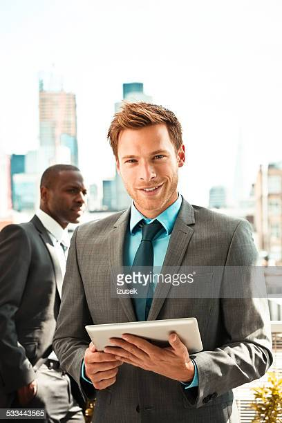 Outdoor portrait of businessman with digital tablet