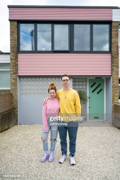 outdoor portrait of caucasian couple in front of modern home - mid adult men stock pictures, royalty-free photos & images