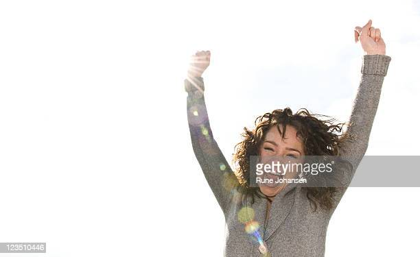 Outdoor portrait of Danish woman, 26 years old, screaming with arms stretched upwards in victory