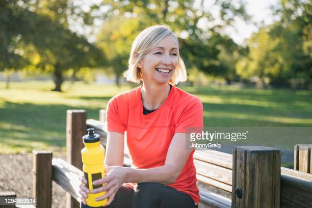 outdoor portrait of early 50s female athlete after workout - clapham common stock pictures, royalty-free photos & images