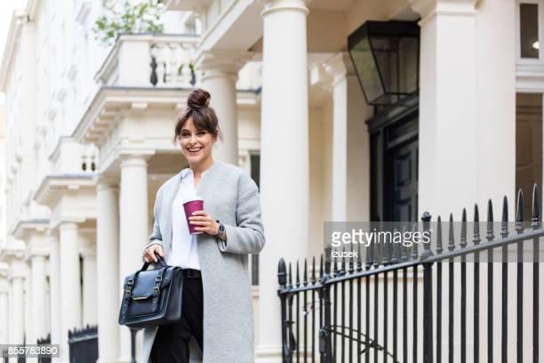outdoor portrait elegante schöne frau stand vor stadthäuser - izusek stock-fotos und bilder