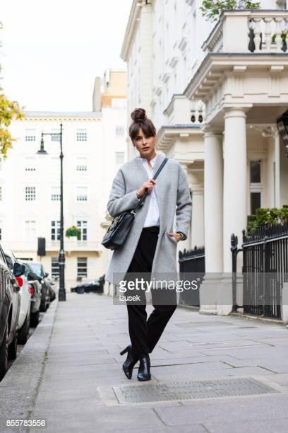 Outdoor portrait of elegant beautiful woman standing in the city street