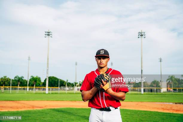 outdoor portrait of hispanic baseball pitcher and ball field - baseball pitcher stock pictures, royalty-free photos & images