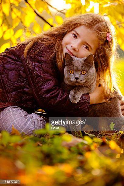 Outdoor Portrait of Little Girl Hugging Her Cat