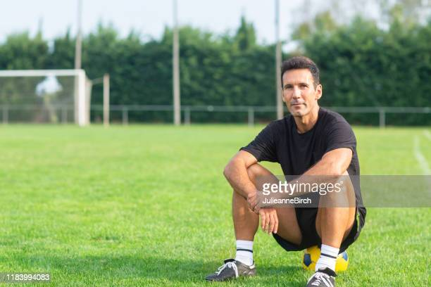 outdoor portrait of mature male footballer sitting on ball - coach stock pictures, royalty-free photos & images