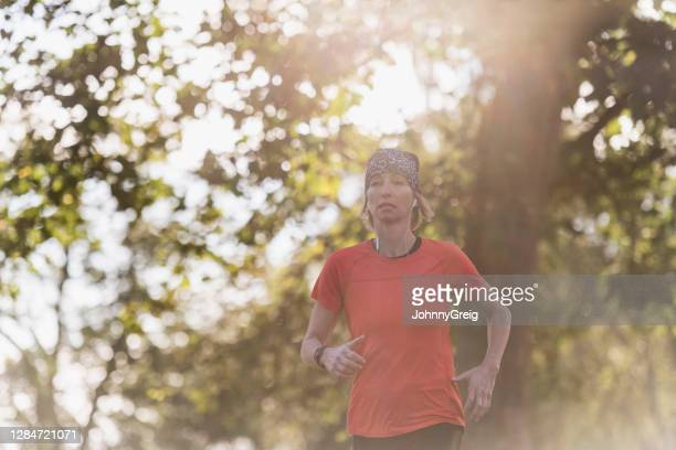 outdoor portrait of mature sportswoman on run in public park - clapham common stock pictures, royalty-free photos & images