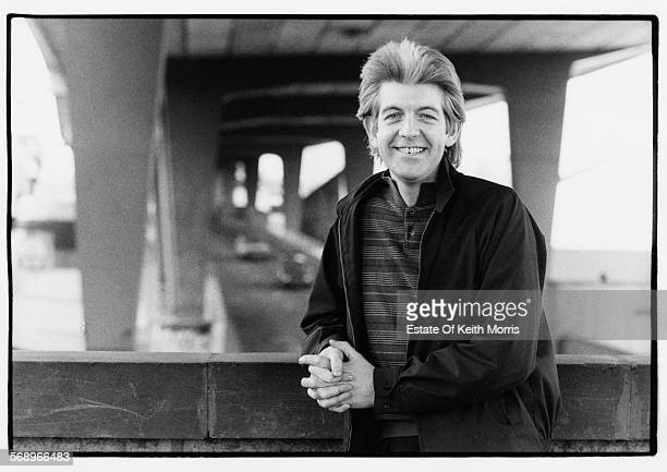 Outdoor portrait of musician Nick Lowe sitting on a bridge circa 1990