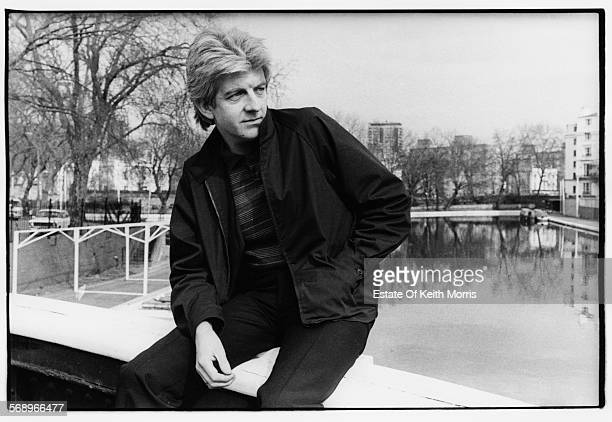 Outdoor portrait of musician Nick Lowe sitting on the edge of a bridge overlooking a river circa 1990