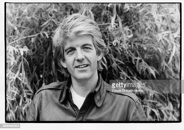 Outdoor portrait of musician Nick Lowe wearing a leather jacket, circa 1990.