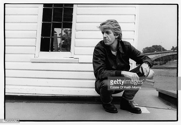 Outdoor portrait of musician Nick Lowe wearing jeans and a leather jacket and smoking a cigarette circa 1990