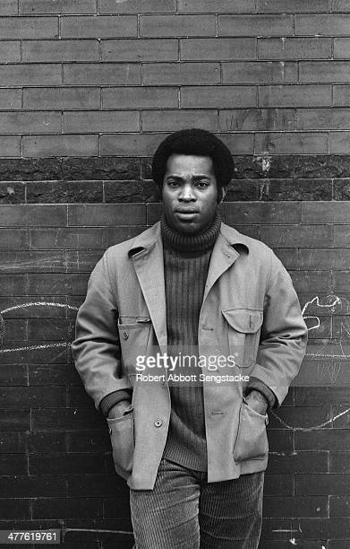 Outdoor portrait of photographer Billy 'Fundi' Abernathy, in a turtleneck and jacket, as he leans against a brick wall, Chicago, Illinois, 1967.