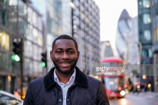 ロンドンの笑顔アフリカの実業家の屋外肖像画 - オイルドジャケット ストックフォトと画像