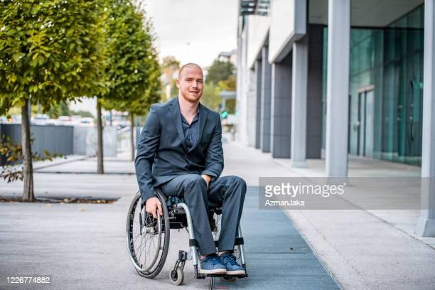 verticale extérieure du travailleur d'entreprise de sourire dans le fauteuil roulant - seulement des adultes photos et images de collection