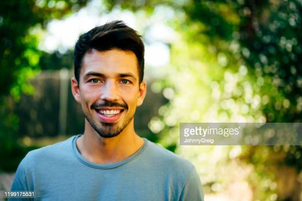 retrato ao ar livre do homem espanhol de sorriso em 20s meados de - decote redondo decote - fotografias e filmes do acervo
