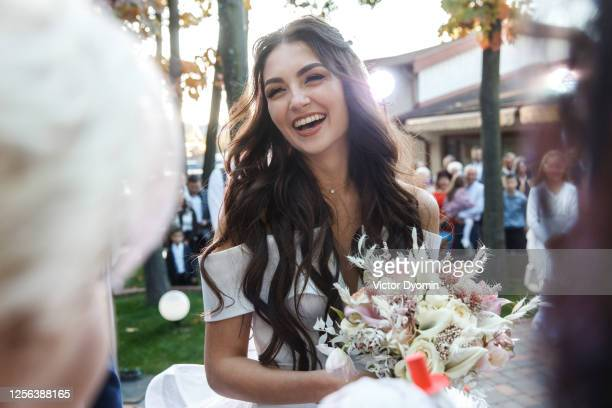 outdoor portrait of the smiling bride among guests - guest stock pictures, royalty-free photos & images