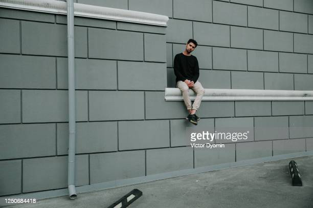 outdoor portrait of the stylish young man on the wall - geometriestunde stock-fotos und bilder