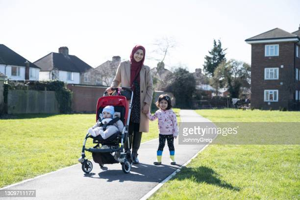 outdoor portrait of young british asian family enjoying walk - religious dress stock pictures, royalty-free photos & images