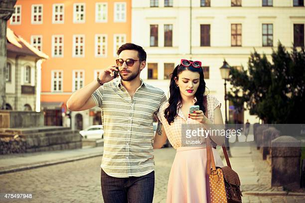 Outdoor portrait of young couple in the city using phones