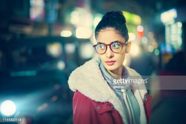 Outdoor portrait of young woman in street at night.