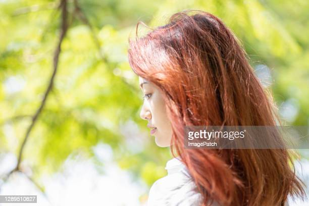 outdoor profile headshot of beautiful young women with red hair - dyed red hair stock pictures, royalty-free photos & images