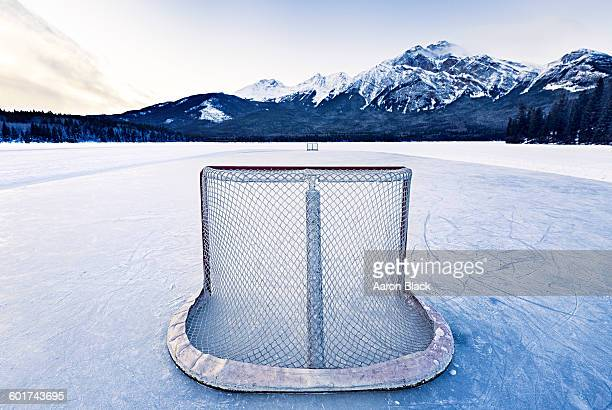 Outdoor rink on lake with mountain background