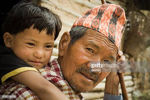 Outdoor rural image of grandchild on grandfather's piggyback.