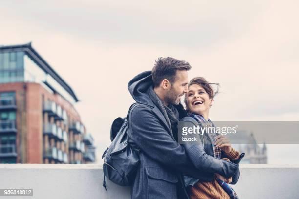 outdoor shot of happy couple embracing on bridge in london - izusek imagens e fotografias de stock