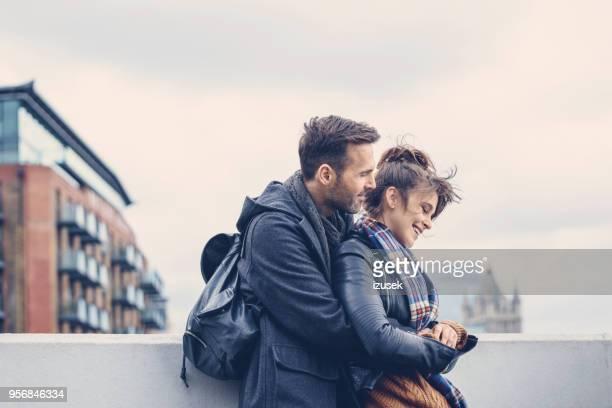 outdoor shot of happy couple standing on bridge in london - izusek imagens e fotografias de stock