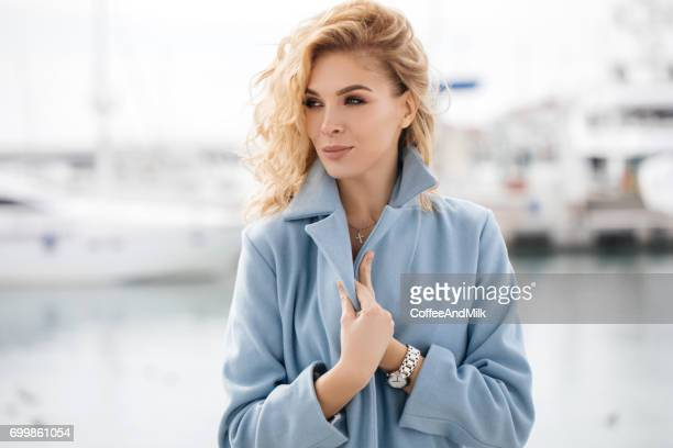 outdoor shot of young beautiful woman on a pier - coat stock pictures, royalty-free photos & images