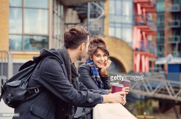 橋の上のホットド リンクを飲む若いカップルの屋外撮影
