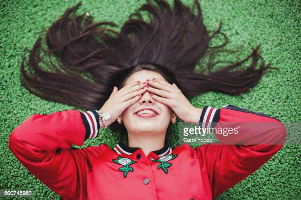 outdoor shot of young woman lying on floor covering eyes with hands - multi colored coat stock photos and pictures