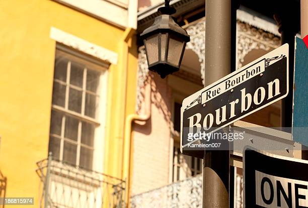 outdoor street sign on bourbon street - mardi gras party stock photos and pictures