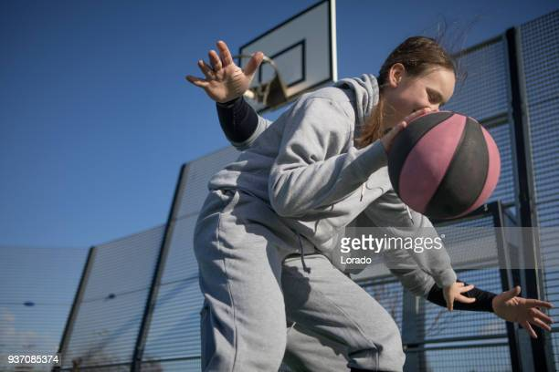 Outdoor urban basketball training session between male father coach and female daughter player