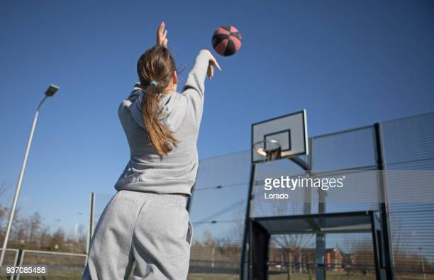 outdoor urban basketball training session for individual female teenage girl streetball player - shooting baskets stock photos and pictures
