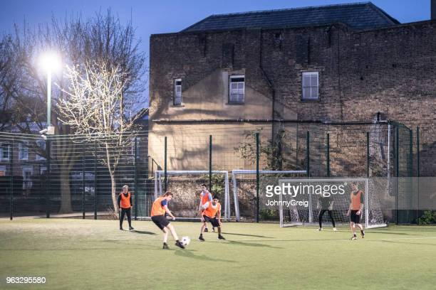 Outdoor urban floodlit pitch with group of men playing football