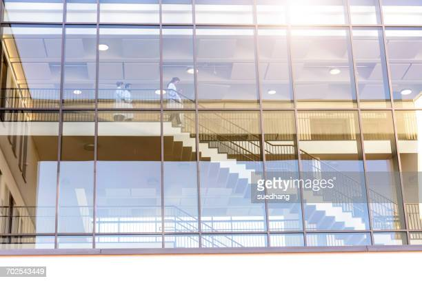 outdoor view of male and female doctors moving down hospital stairway - medical building stock pictures, royalty-free photos & images