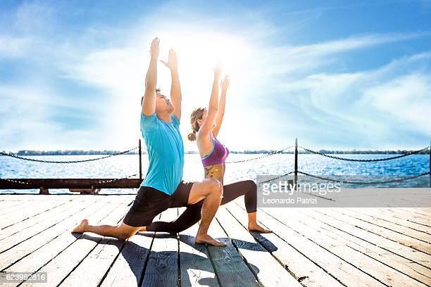 Outdoor yoga lessons. Man and woman exercising
