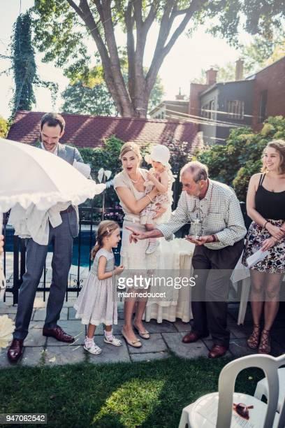 baptême de bébé en plein air avec la famille et le célébrant. - baptême photos et images de collection
