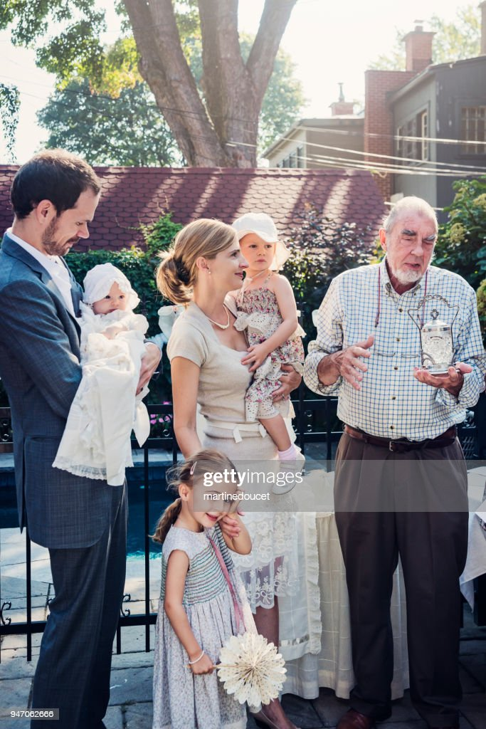 Outdoors baby baptism with family and celebrant. : Stock Photo
