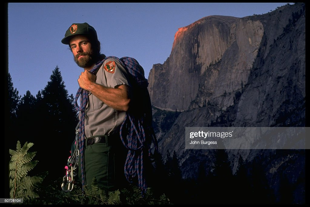 Feature. Portrait of Yosemite National Park Ranger Mark Fincher alone w. mountain climbing gear in front of peak.