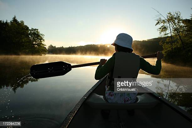 Outdoors girl canoeing in bright sun and morning mist