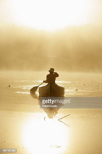 Outdoors girl paddling canoe on lake in misty sunrise backlit