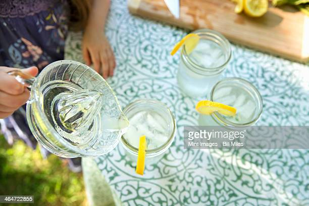 Outdoors in summer. Making lemonade. Overhead shot of lemonade glasses with a fresh slice of lemon in the edge of the glass. A child pouring the drink from a jug.