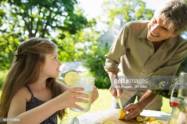 Outdoors in summer. On the farm. Children and adults working together. A girl and an adult man making lemonade. Cutting up fresh fruits.