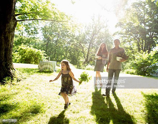 Outdoors in summer. On the farm. Two adults carrying cartons of fresh vegetables and plants. A girl carrying bunches of fresh herbs.