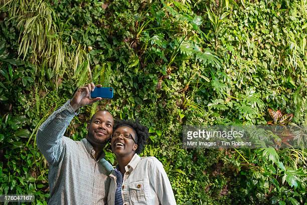 outdoors in the city in spring. an urban lifestyle. a couple standing in front of a wall covered with lush thick foliage. - thick black woman stock photos and pictures