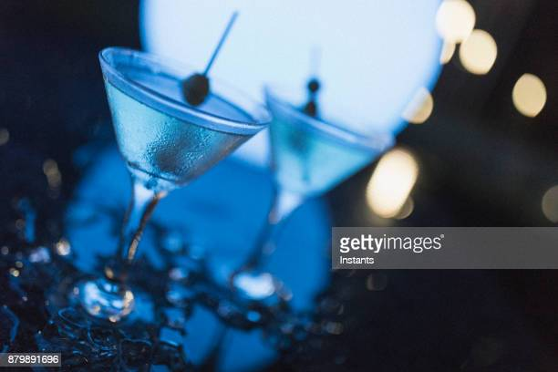 outdoors night shot of two martinis with olives, as shot in nassau. - cocktail stock pictures, royalty-free photos & images