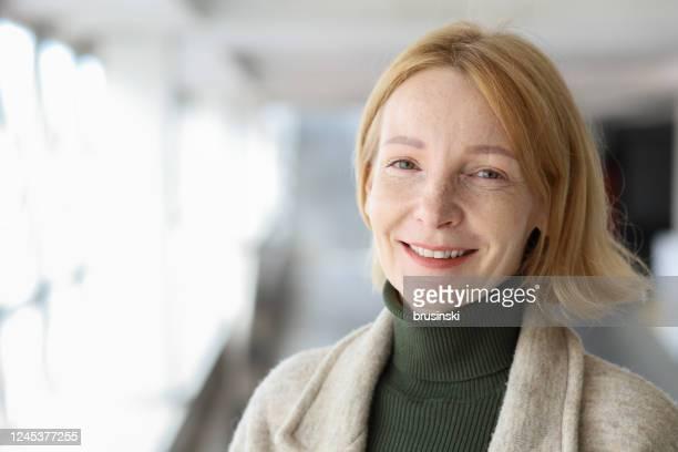 portrait extérieur d'une femme rousse de 45 ans - une seule femme d'âge mûr photos et images de collection