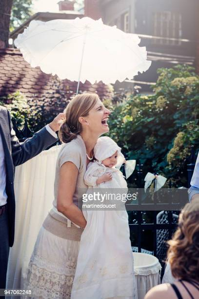 outdoors traditionnal baby baptism with family. - catholic baptism stock pictures, royalty-free photos & images
