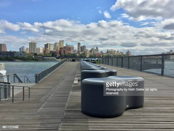 outdoors urban waterfront park with modern plastic seats lined in a row on a wood pier overlooking the east river and brooklyn nyc - south street seaport stock photos and pictures